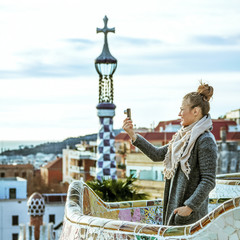 tourist woman at Guell Park taking photo with digital camera