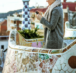 tourist woman at Guell Park viewing photos on camera