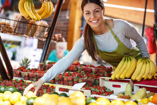 Young attractive fruit market saleswoman selecting fresh fruit and preparing for working day.