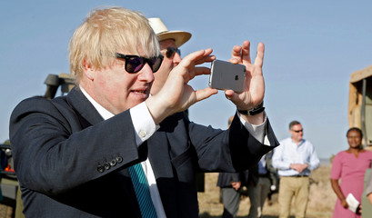 Britain's Foreign Secretary Boris Johnson uses his phone to take a picture of elephants at the Lewa wildlife conservancy sprawling over the Laikipia plains in northern Kenya