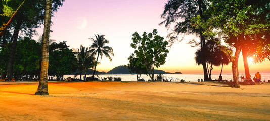 Patong beach at sunset in Phuket island famous tourists destination in Thailand - Silhouette of palm trees and people relaxing on the shore at dusk falling light - Tropical holidays concept