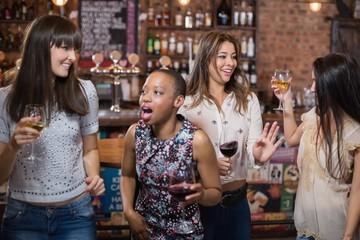 Female friends dancing at pub