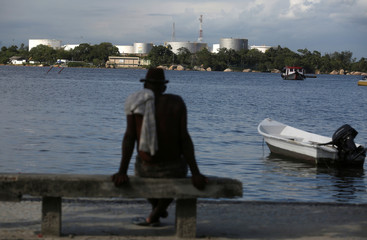 A man sits on a beach with the Petrobras fuel tanks in the background in the Guanabara bay in Rio de Janeiro