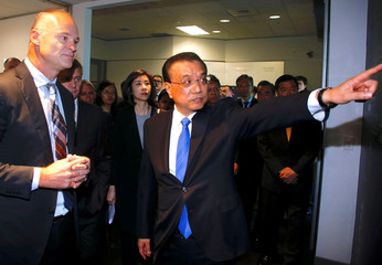 Chinese Premier Li Keqiang reacts as he talks with Stuart Broadhurst during a tour of the Fisher and Paykel manufacturing plant in Auckland, New Zealand