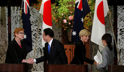 Australia's Defense Minister Payne and Foreign Minister Bishop shake hands with Japan's Foreign Minister Kishida and Defense Minister Inada in Tokyo