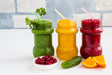 Three fresh smoothies, red, yellow and green ones in glass jars on the white wooden table
