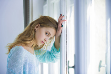 Pretty girl with blue eyes standing at window