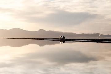 Vehicle driving down long reflective lake road