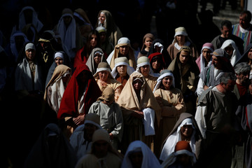 "Worshippers re-enact the ""Stations of the Cross"" during a procession on Good Friday in Ourem"