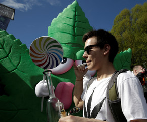 People pose for photos next to a person wearing a pot-leaf costume at the annual 4/20 marijuana event at Sunset Beach in Vancouver, British Columbia, Canada