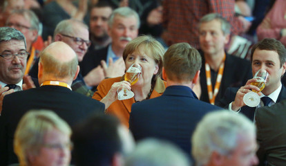 German Chancellor Merkel drinks beer during the CDU's political Ash Wednesday in Demmin
