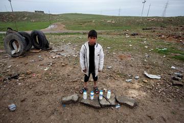 A boy sells milk on the street near the city of Mosul