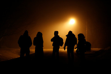 Migrants stand on a residential street after crossing the Canada-U.S. border in Emerson