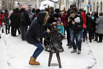 A woman has her picture taken with the 'Fearless Girl' statue which stands in front of Wall Street's Charging Bull statue is seen in New York