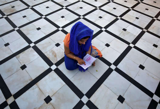 A Hindu woman reads a religious scripture as she prays inside a temple during Navratri festival in Jammu