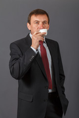 Confident mature businessman standing in front of a grey background taking a cup of coffee