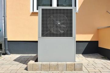 Luftwärmepumpe für Heizung und Warmwasser vor einem Niedrigenergiehaus