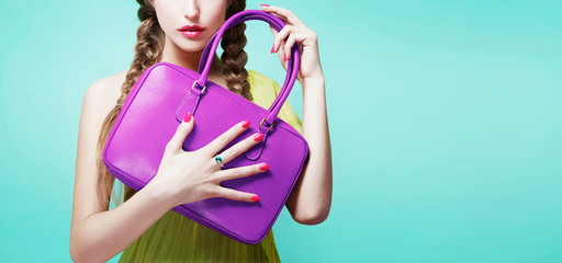 Young girl holding her purple color handbag purse isolated on aqua blue background with copy space.