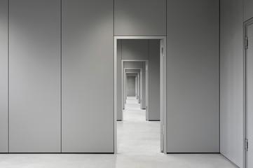 Empty corridor passing through doorways at office