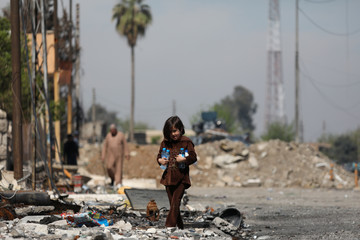 A girl carrying bottles of water walks among debris on a street of Mosul