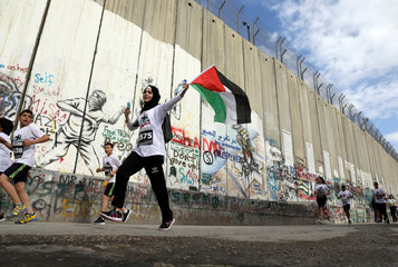 Participants run past the Israeli barrier during the annual Palestine Marathon in the West Bank town of Bethlehem