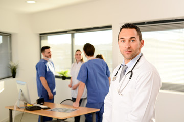 portrait of a young male doctor in hospital office with medical team in background