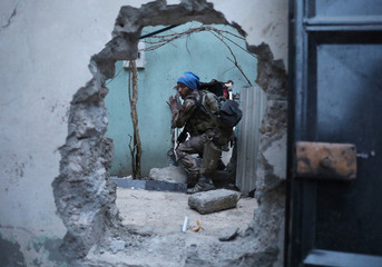 An Iraqi Special Forces soldier moves through a hole as he searches for Islamic State fighters in Mosul