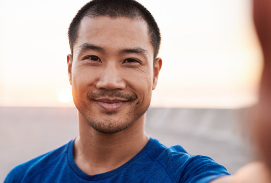 Athletic Asian man smiling while out for a morning run