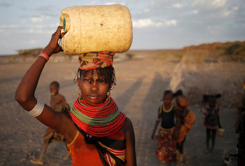 A woman carries a water canister in a village near Loiyangalani