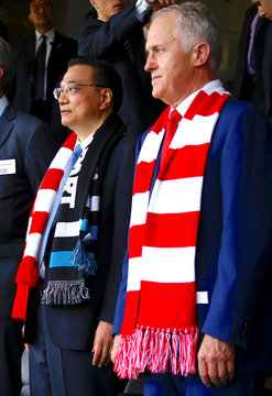 Australia's Prime Minister Malcolm Turnbull stands with Chinese Premier Li Keqiang before the start of an Australian Football League (AFL) game at the Sydney Cricket Ground in Sydney