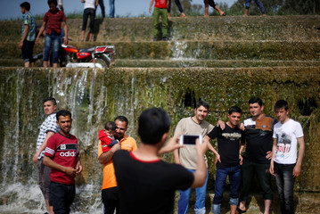 "Iraqi people take pictures as they enjoy their Friday holiday at Shallalat district (Arabic for ""waterfalls"") in eastern Mosul"
