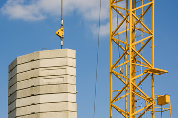 Tower construction crane and concrete blocks against the sky background.