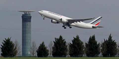 An Airbus A330 Air France airplane takes off past a control tower at the Charles-de-Gaulle airport in Roissy during an air traffic controller strike