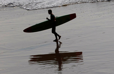Surfer leaves the water after a surf session during an unusually warm spring day on Biarritz beach, southwestern France