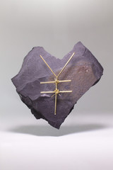 Yen sign made of metallic wire on heart shape stone against white background