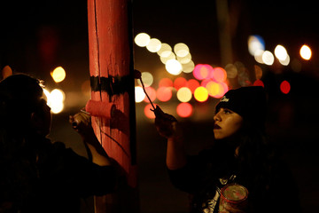 Activists paint a black cross on a pink background on a lamp post to remember women who went missing or were killed, as they mark International Women's Day in Ciudad Juarez