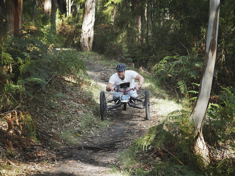 Man riding modified bicycles on forest path