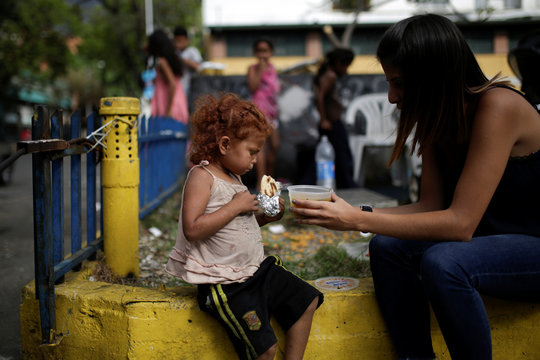 A volunteer of Make The Difference (Haz La Diferencia) charity initiative gives a cup of soup and an arepa to a homeless child  in a street of Caracas