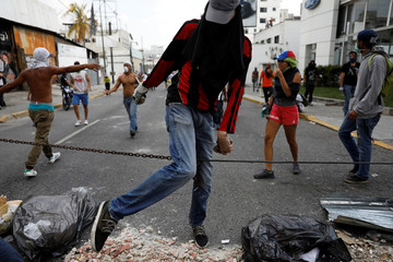 Opposition supporters block the street with a chain during a rally against Venezuela's President Nicolas Maduro in Caracas