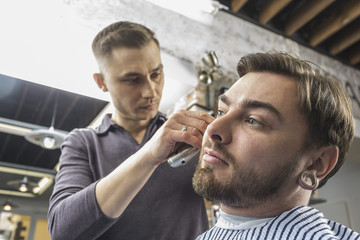 Low angle view of male hairdresser cutting young customer's hair at barber shop