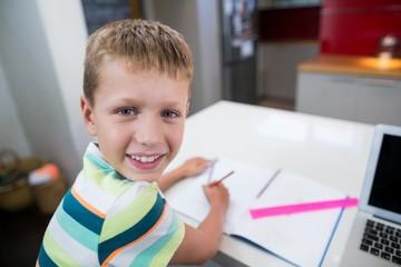 Smiling boy doing his homework in kitchen