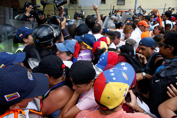 Opposition supporters clash with riot police during a protest against Venezuela's President Nicolas Maduro's government in Caracas