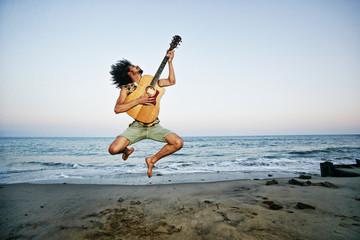 Mixed Race man playing guitar and jumping at beach