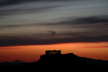 The ancient Parthenon temple is illuminated during sunset atop the Acropolis hill in Athens