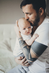 Caucasian father with tattoos on arms kissing baby son