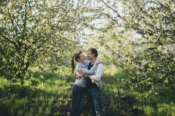 Caucasian couple kissing under flowering trees