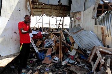 A Somali trader stands outside his shop destroyed near the scene of a suicide bomb explosion at the Wadajir market in Madina district of Somalia's capital Mogadishu