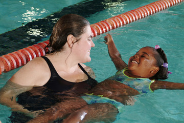 Woman teaching girl to swim in swimming pool