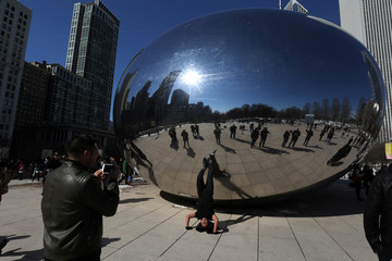 A man does a head stand as he poses for a photo at the Cloud Gate public sculpture on a sunny day