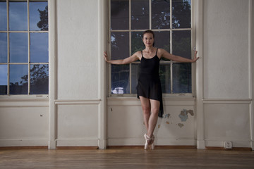 Asian ballerina posing at window in studio
